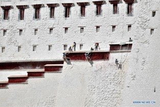 Workers paint wall of Potala Palace in Lhasa, SW China's Tibet
