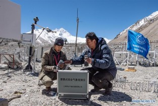 Staff members of region's meteorological bureau work at automatic meteorological station of Mount Qomolangma base camp